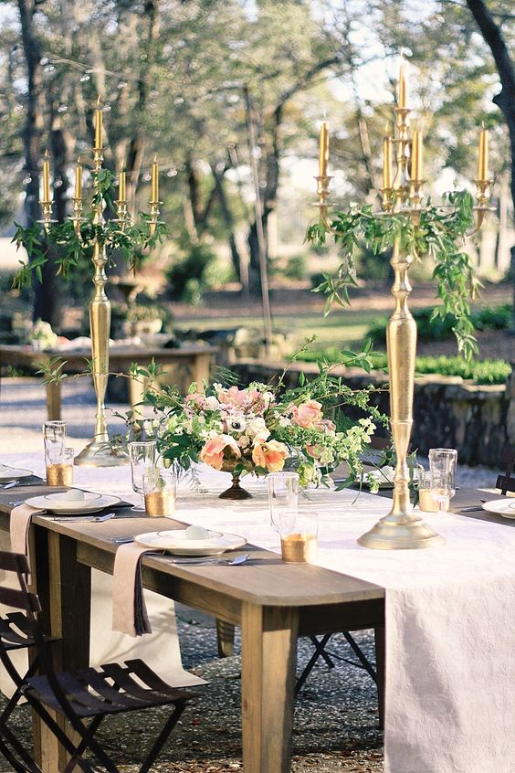 Romantic courtyard tabletop with pretty florals and tall gold candelabras. Photographed at RiverOaks Charleston in Charleston, SC by Justina Bilodeau. #wedding