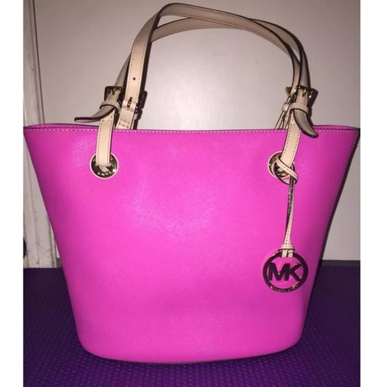 "Authentic Michael Kors Jet Set Saffiano Handbag Used only a few times, still in great condition!  Material: Saffiano Leather in Pink  Shoulder style bag features double handles for easy carrying Quality leather  Logo patterned lining Button close, goldtone hardware Dimensions: 10""H x 15""W x 9""D Michael Kors Bags Shoulder Bags"