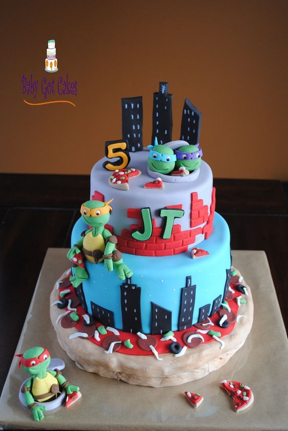 This is a 3 tier Ninja Turtle themed cake covered...