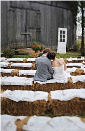 Bride and groom pictured on hay bale seating draped and tied in white cotton.  Using twine to secure the cotton is a great idea, keeps your seating looking clean.