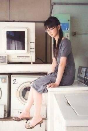 グレーのワンピースに眼鏡をかけて洗濯機の上に座っている多部未華子の画像