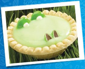 Alligator Pie  12 Tenderflake Tart Shells  1 package instant pistachio pudding mix  (or vanilla dyed green)  24 green Smarties®  White small point decorating gels