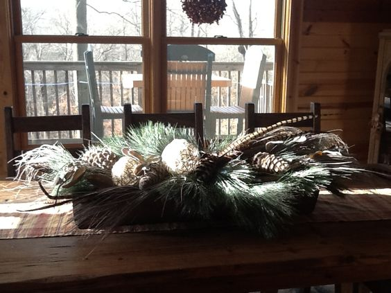 Rustic table centerpiece, pine cones, pheasant feathers and snow covered balls