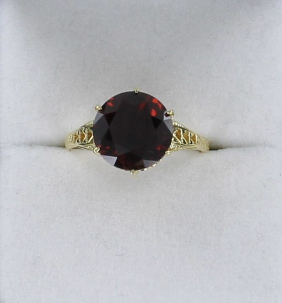 14KT GARNET RING A SIMPLE AND ELEGANT ANTIQUE-INSPIRED GARNET RING. CRAFTED IN 14KT YELLOW GOLD, THE BEAUTIFULLY-FACETED DEEP RED WINE-COLORED GARNET IS SET IN A LOVELY BASKET, AND THERE IS MARVELOUS ENGRAVING ON THE SHANK. $595