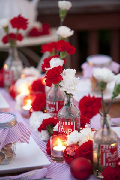 A mixture of carnations, red holiday ornaments, and candles make ...