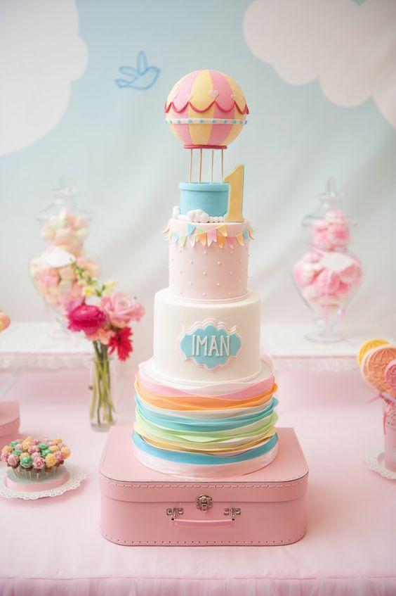 Espectacular tarta infantil de tres pisos, forrada con fondant, y con globo en lo alto.