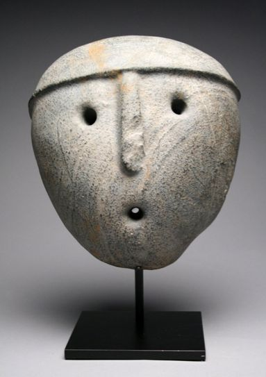 """Auction house description: Pre-Columbian, Aguada Culture, Argentina, ca. 1000 CE. An important and dramatic minimalist stone mask of this rare culture hardly known to us due to its lack of monumental architecture. Its mouth is pointed because it's a shamanic mask of a """"life-giver,"""" life that is blown by a shaman into matter that needs healing. 10""""H x 9""""W.:"""