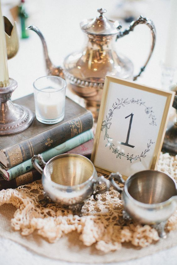 centerpieces with vintage books and silver accents