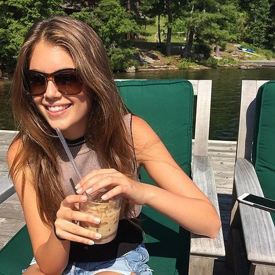 Kaia had a smile on her face and a cold drink in her hand.