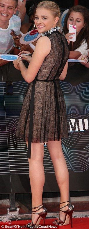 Style chameleon: Chloë donned a semi-sheer black lace sleeveless frock with a floral high neckline and a pair of strappy metallic heels