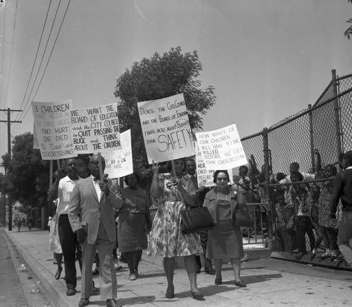Protest to improve safety for schoolchildren, Los Angeles, 1966. Pictured are Leon Washington (front left) and Marnesba Tillmon Tackett (far right). Tackett, a civil rights activist, worked to desegregate Los Angeles public schools. Harry Adams Collection. Institute for Arts and Media Photographs.