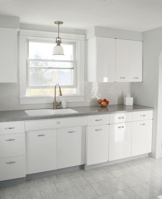 This kitchen creates a fully white on white look that's stylish and elegant though it seems a little bit too clean to be real. The coutertops definitely help with that by adding a bit of color.