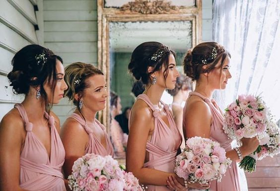 A truly touching happy ever after moment when time stood still as her gorgeous bridesmaids look on at their beautiful bride @sarah_tilse with her handsome groom!  Bridesmaids looking amazing in their Goddess By Nature signature multiway ballgowns in the best selling dust me pink colour that looks absolutely stunning paired with these gorgeous pastel pink roses  Stockist WhiteRunway.com   Kieran Moore Photography   www.goddessbynature.com info@goddessbynature.com For your nearest stockists…