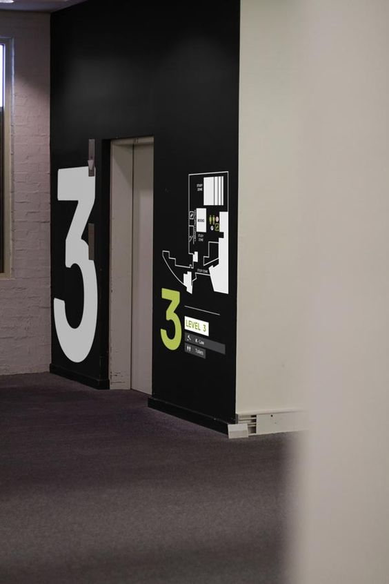 Oversized numbers and floor plan next to an elevator. Visit the slowottawa.ca boards