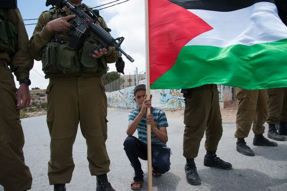 Photo shows boy holding Palestine flag crouching between Israeli soldiers