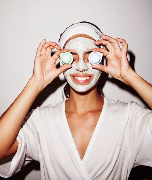 Woman with face mask holding up skincare capsules