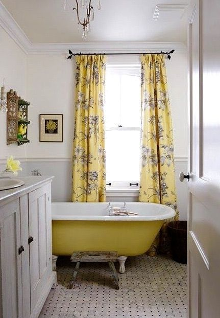 Yellow clawfoot tub in beautiful country style bathroom with vintage vanity and marble floors #SarahRichardson #yellowbathroom #clawfoottub