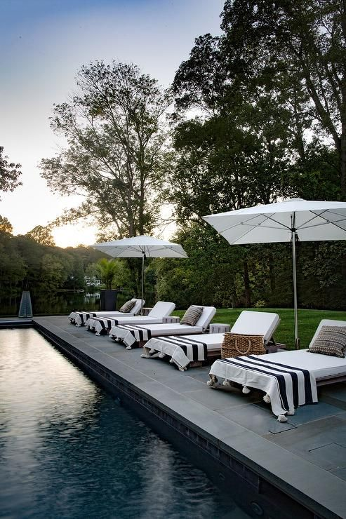 White Umbrellas Accent Teak Adjustable Loungers Topped With White Cushions Complemented With Black And Wh Outdoor Pool Furniture Pool Lounge Chairs Pool Houses