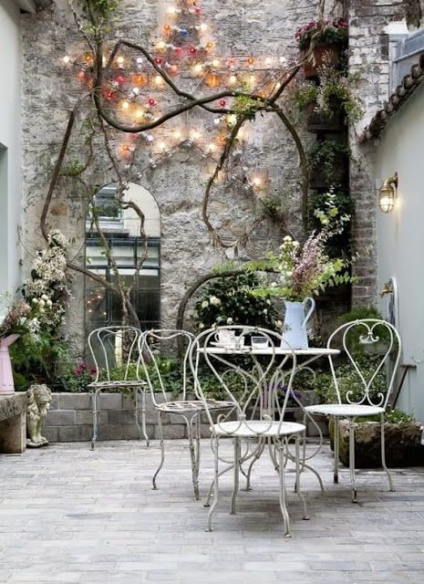 French farmhouse decor and French Country style inspiration from this Paris courtyard with stone wall, fairy lights, mirror, and bistro furniture. #parisdecor #frenchcountrydecor #frenchfarmhouse #frenchcourtyard #patiodecor #outdoordecor #gardeninspiration
