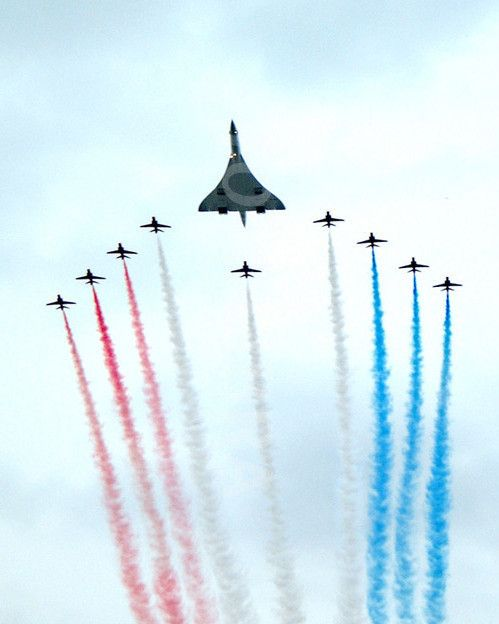 A British Airways Concorde supersonic airliner escorted by the red Hawks of the RAF Red Arrows.
