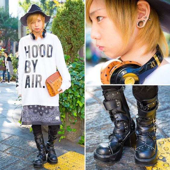 20-year-old Kenchu in Harajuku wearing a Hood By Air top with a bandana skirt, ripped jeans, studded boots, and clutch/headphones by MCM.