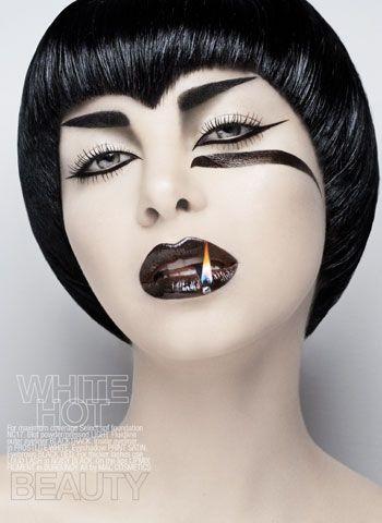 Women's HairCut Short Rounded w/Point in Bang  Women's HairColor Black  MakeUp Pale Face/Black Heavy Eyebrow/ Black Streak Under Eye Black Lips w/Lit Match.