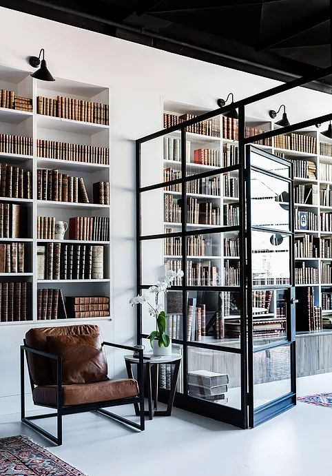 Glass pained wall seperating office to library. Via Busatti Design