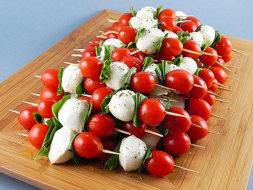 brochettes de tomates cerises et de billes de mozzarella avec des feuilles de basilic
