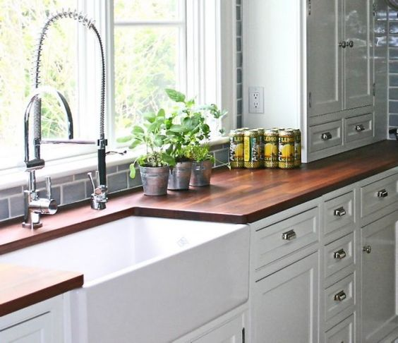 Wood Kitchen Countertops With White Ceramic Farmhouse Sink Below Spring Loaded Water Faucets