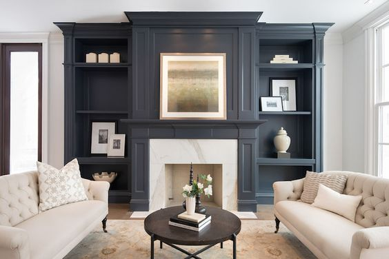 Elegant living room features matching cream tufted sofas on caster legs facing each other across from a round iron coffee table atop a blue and cream rug. Transitional living room boasts gray built-in shelves flanking a gray fireplace mantle accented with white marble surround.