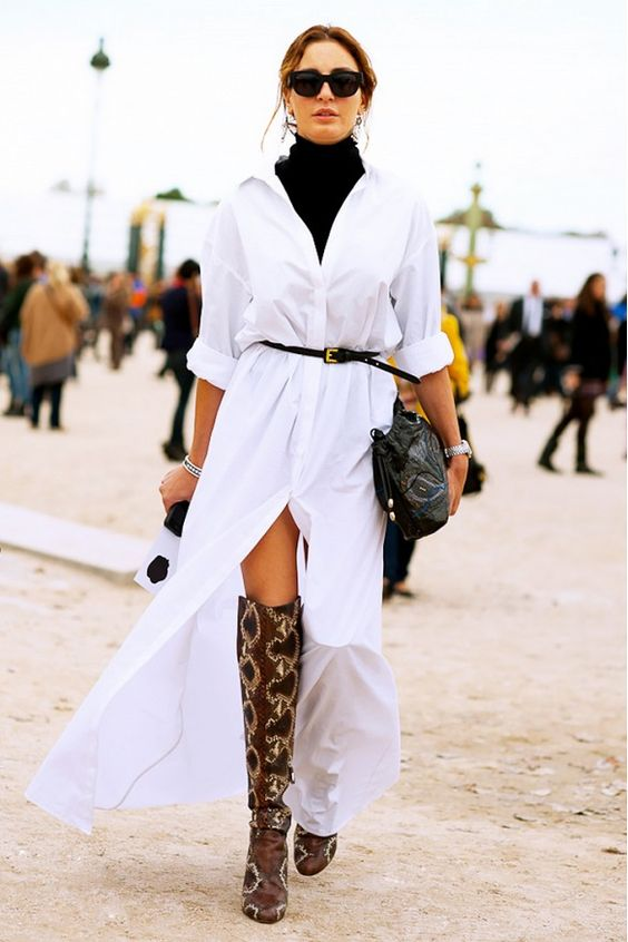Turtleneck layered underneath a floor-length shirtdress and accessorized with a skinny belt and thigh-high boots.: