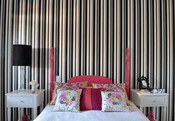 A moradora inovou o quarto de hóspedes. Investiu em um papel de parede listrado. A cama de 1930, herdada, recebeu pintura automotiva pink após ser restaurada, como os criados-mudos, tingidos de branco
