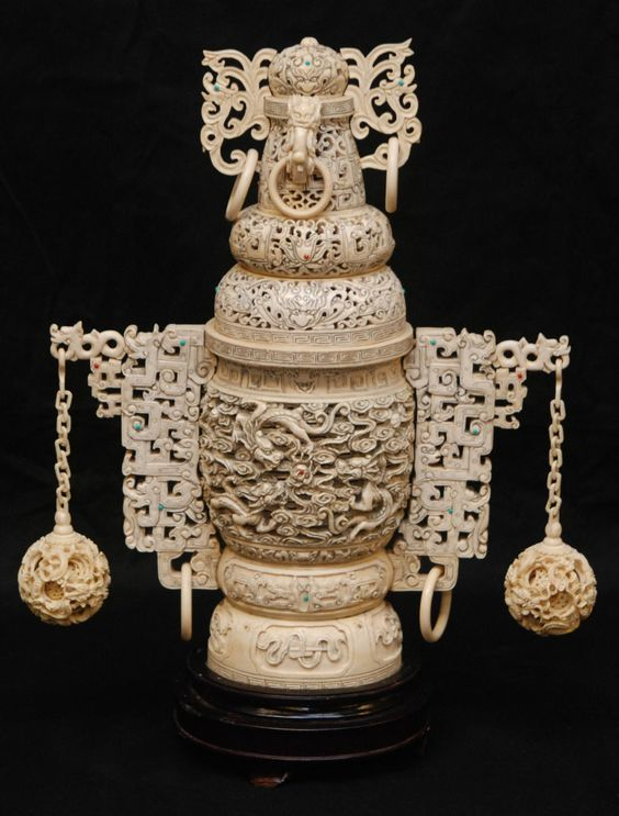 "CHINESE CARVED IVORY CONCENTRIC DRAGONS URN Antique Chinese hand carved ivory urn having a fully reticulated design throughout depicting dragons. Has figural dragon handles to cover with relief rings. Has dragons with clouds and jewel design to body with screen archaic handles to each side. Hanging from each handle is a concentric ball on chain. Includes fitted wooden base. 19th century. Measures 17 3/4"" height x 14"" width + 2 1/2"" base height"