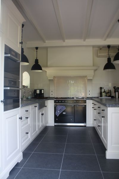 I love this kitchen with a cooking hearth with Dutch 'witjes' tiles as backsplash. Love the big gray stone tiles and the white ceiling beams too.