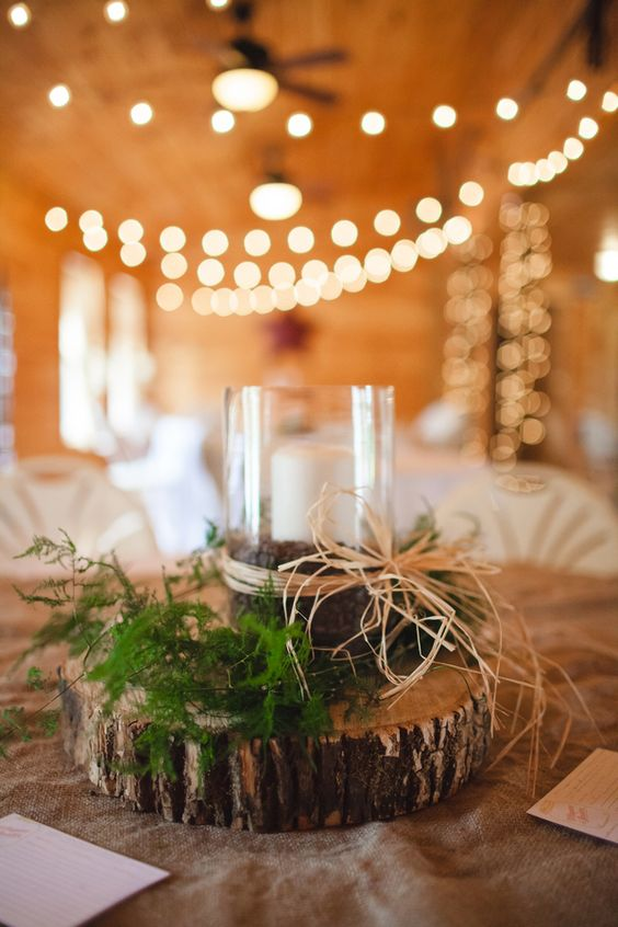 tree slices are topped with clear candle holders and wrapped with raffia and a touch of evergreen placed at the base - thereddirtbride.com- see more of this wedding here