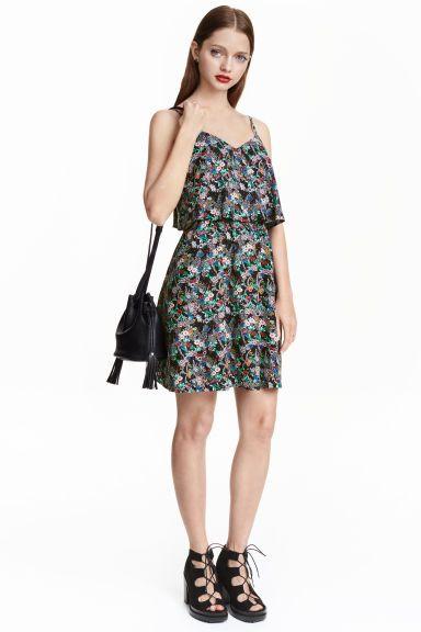 Рокля без ръкави: Къса рокля от вискоза с регулиращи се презрамки, широк волан в горната част, еластичен шев на талията и леко разкроена пола.