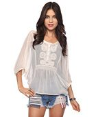 A flowing sheer top featuring a decorative partial button placket with detailed trim. 3/4 dolman sleeves with buttoned wrists. Elasticized waist panel. Woven. Unlined. Lightweight.   *Cami not included  .    DETAILS:  - 24' approx. length from high point shoulder to hem, 46' chest, 42' waist, 18' sleeve length from high point shoulder  - Measured from Small  - 100% polyester  - Hand wash, line dry  - Imported