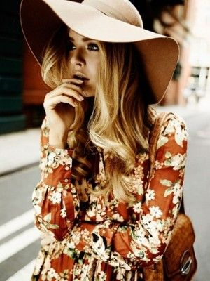 70's fashion consisting of chic wide sun hats, floral dresses, and brown leather satchels.: