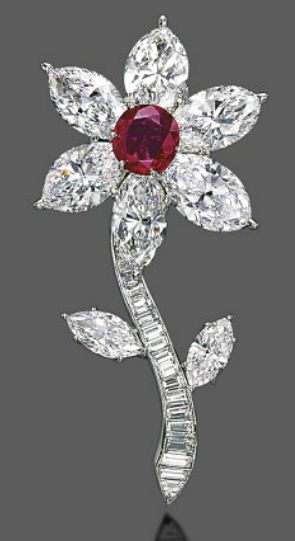 A FINE RUBY AND DIAMOND BROOCH   Designed as a flower, centering upon an oval-shaped ruby, weighing approximately 5.56 carats, extending six marquise-shaped diamond petals, weighing approximately 5.63, 5.11, 5.02, 4.98, 4.08 and 4.03 carats, to the detachable baguette-cut and marquise-shaped diamond stem, mounted in platinum and gold, 7.0 cm