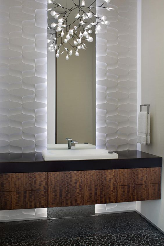 Though the palette is neutral, this small powder room is anything but plain. A textured wall treatment is made more pronounced by a backlit mirror. Meanwhile, the warm wood vanity floats above a pebbled floor, creating a dynamic space with interest packed into every inch.