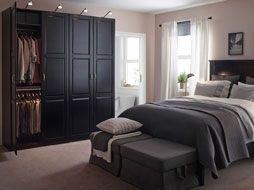 Ein großes Schlafzimmer mit einem großen PAX Kleiderschrank mit UNDREDAL Türen in Schwarz und einem UNDREDAL Bettgestell in Schwarz