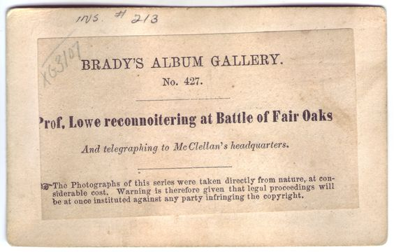 """Prof. Lowe reconnoitering at Battle of Fair Oaks. Two-sided card featuring photograph of man in a hot-air ballon tethered above a Union Army camp on one side and description of the photograph and copyright statement on back. Photograph is characterized as belonging to famous photographer, Matthew Brady. Photograph card 3"""" x 5""""."""
