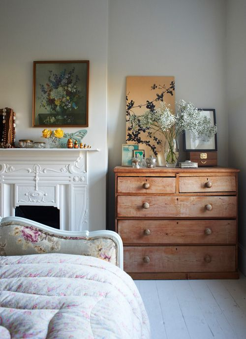 white walls, floral upholstered foot board and wood drawers