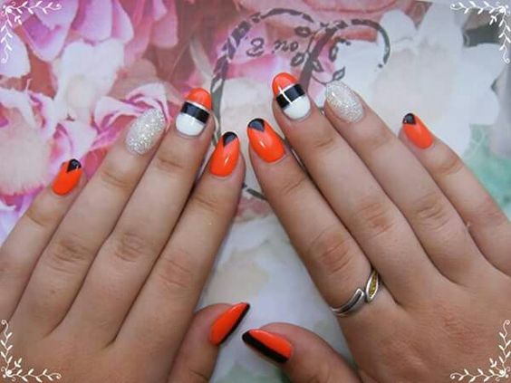 Summer creative orange nails. Have fun this summer and enjoy the beach with cool orange,black and white manicure. The glitters shine on the dark nights,be awesome