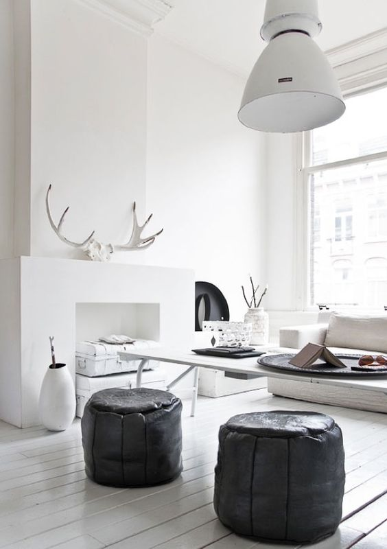 Scandinavian modern style room with stark white walls, black ottomans, and glossy white wood floors. Antlers on fireplace and #rusticdecor
