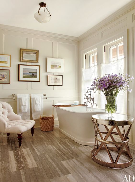 Paintings of Long Island are grouped in a bath at a Hamptons home, creating the perfect summer feel.