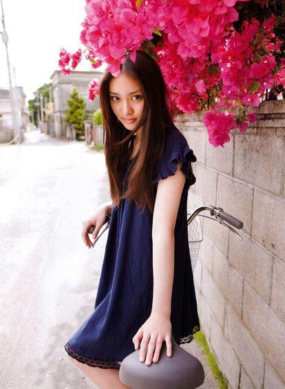 花の下に立っているブルーのワンピースを着た武井咲
