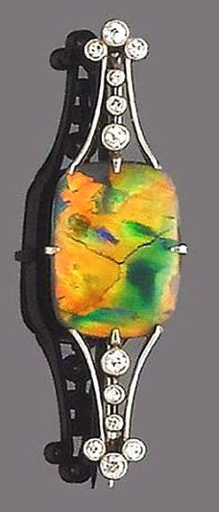 An opal and diamond brooch, circa 1920 The rectangular opal, between bifurcated shoulders of openwork design with single-cut diamond highlights, length 4.3cm.
