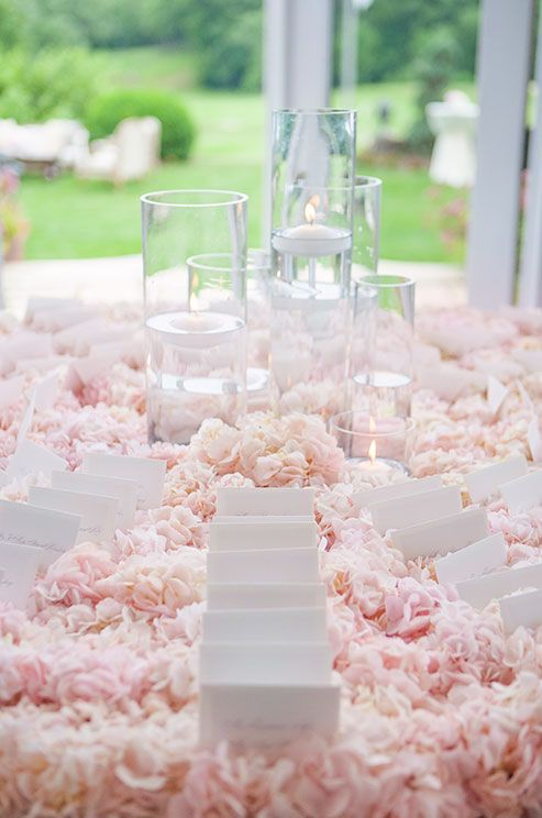 A floral tablecloth is created using pink hydrangeas, making for an incredibly elegant escort card table.: