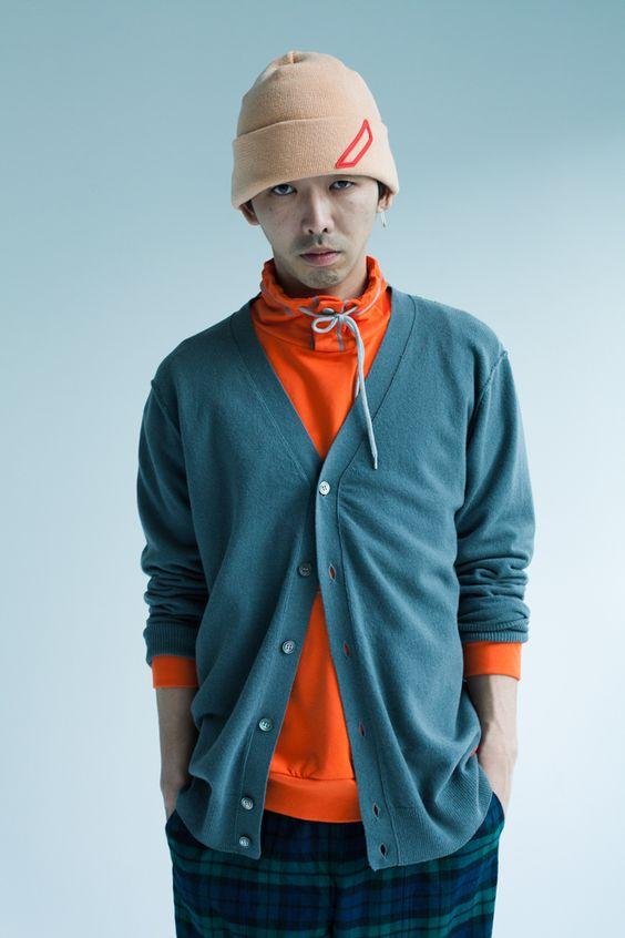 オレンジ色のトップスに青っぽいカーディガン姿の柄本時生